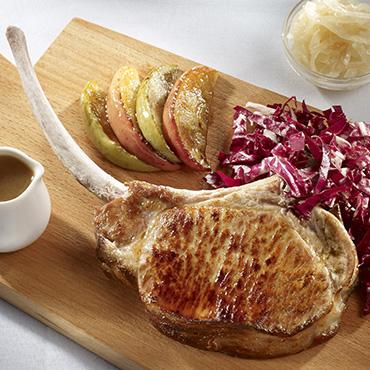 Côte de cochon Tomahawk grillée, pommes acides et jus clair au sirop d'érable